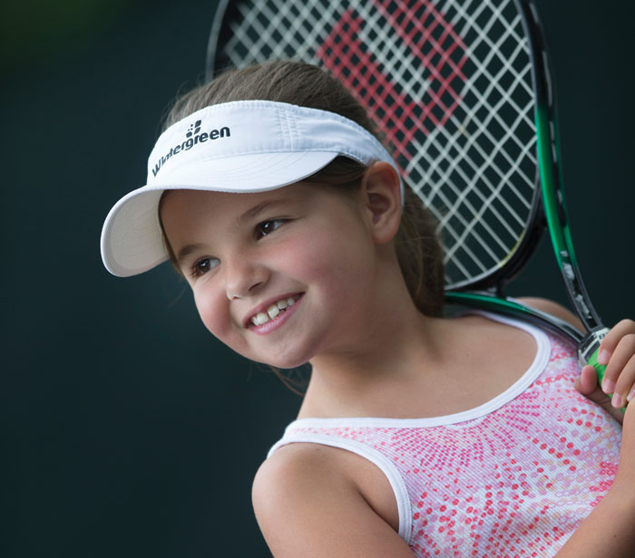 little girl smiling with tennis racquet