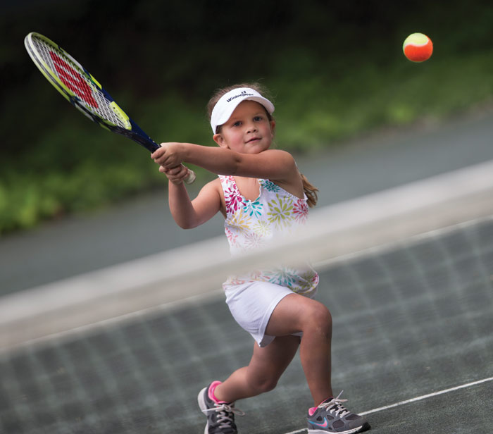 little girl playing tennis